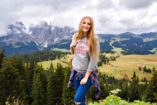 Mooie blonde reizigersvrouw bij bergen. avontuur, alleen reizen Gratis Foto