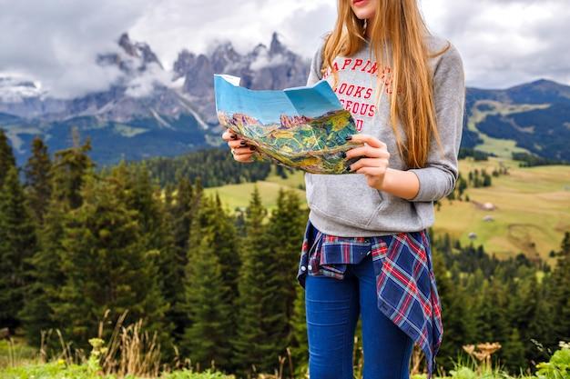 Mooie blonde reizigersvrouw die bij bergen een kaart houden. avontuur, alleen reizen Gratis Foto
