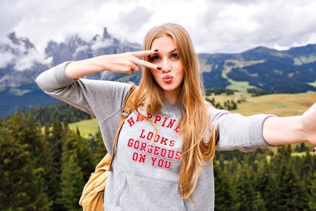 Mooie blonde reizigersvrouw die pret heeft bij bergen. Gratis Foto