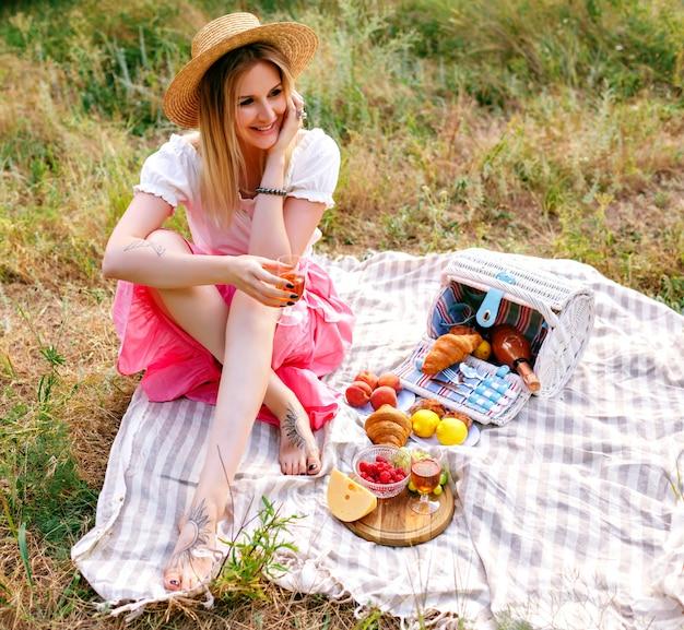 Mooie blonde vrouw, gekleed in vintage stijl outfi, genieten van picknick op het platteland Gratis Foto
