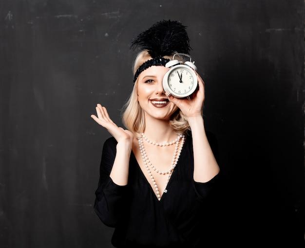 Mooie blonde vrouw in jaren twintig kleding met wekker Premium Foto