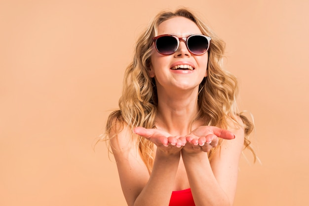 Mooie blonde vrouw in rode bovenkant en zonnebril met omhoog palmen Gratis Foto