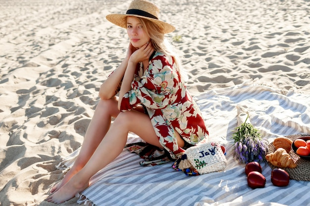 Mooie blonde vrouw in strooien hoed zittend op tropisch strand, genieten van vakantie in de buurt van de oceaan. Gratis Foto