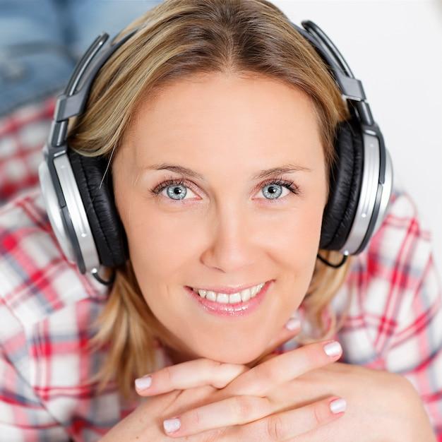 Mooie blonde vrouw luisteren muziek met een koptelefoon Gratis Foto