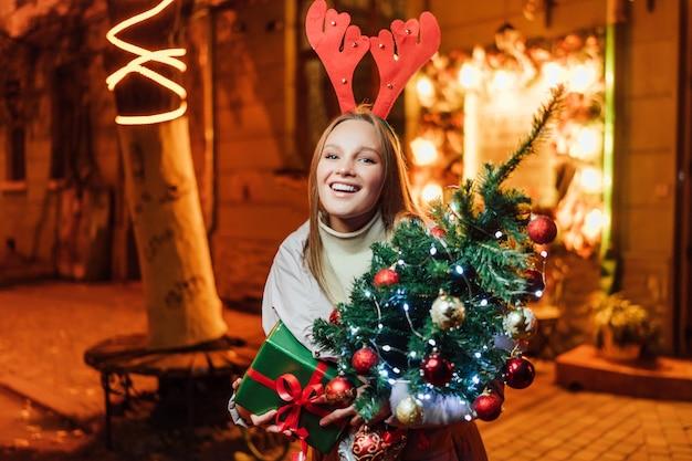 Mooie blonde vrouw met een kerstboom en een cadeau in haar handen lachend Premium Foto