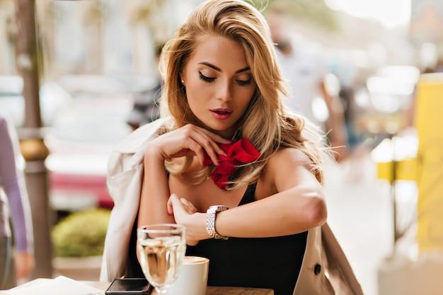 Mooie blonde vrouw polshorloge kijken terwijl het drinken van koffie in openluchtrestaurant. portret van ernstige dame die met rode sjaal op vriend wacht die laat is. Gratis Foto