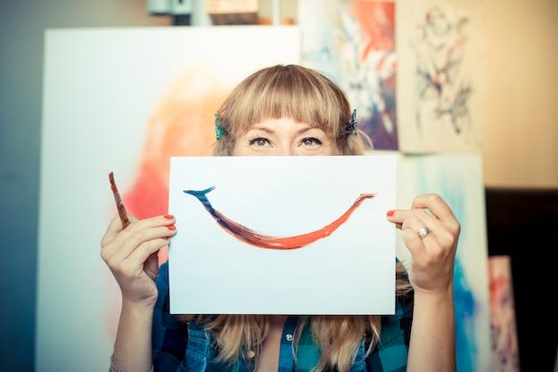 Mooie blonde vrouw schilder glimlachen Premium Foto
