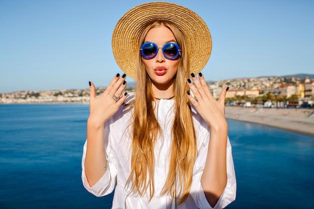 Mooie blonde vrouw trendy strooien hoed en blauwe zonnebril dragen Gratis Foto