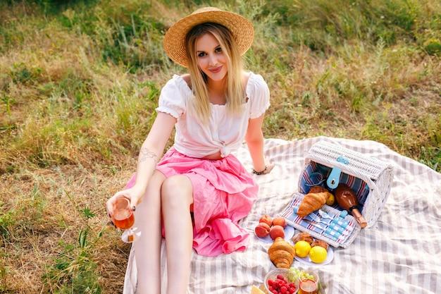 Mooie blonde vrouw vintage stijl outfit dragen, genieten van picknick op het platteland in franse stijl, wijn drinken met croissants en fruit Gratis Foto