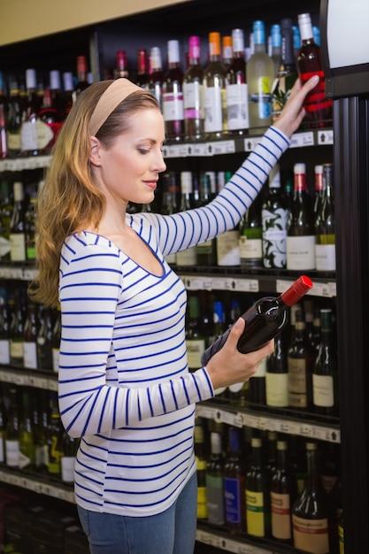 Mooie blondevrouw die een fles rode wijn houden Premium Foto