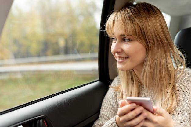 Mooie blondevrouw die een telefoon houden Gratis Foto