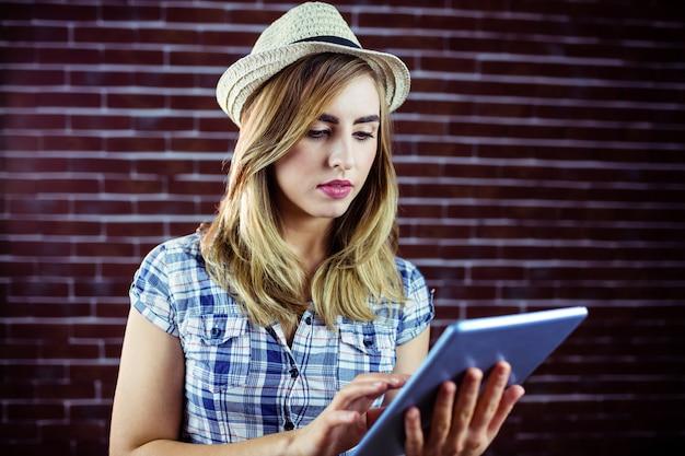 Mooie blondevrouw die tablet gebruiken Premium Foto