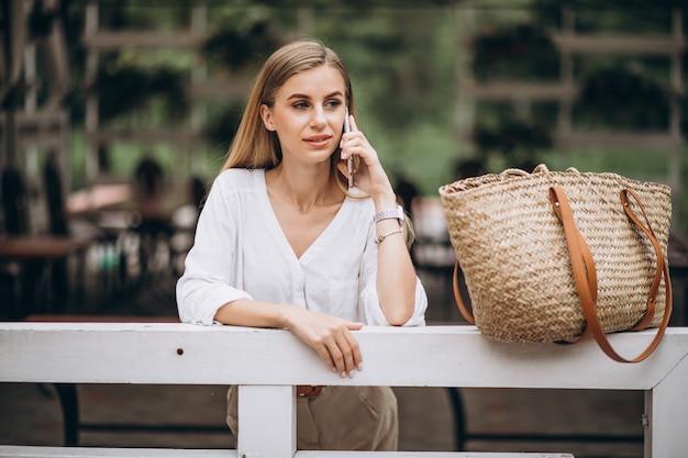 Mooie blondevrouw die telefoon buiten in park met behulp van Gratis Foto