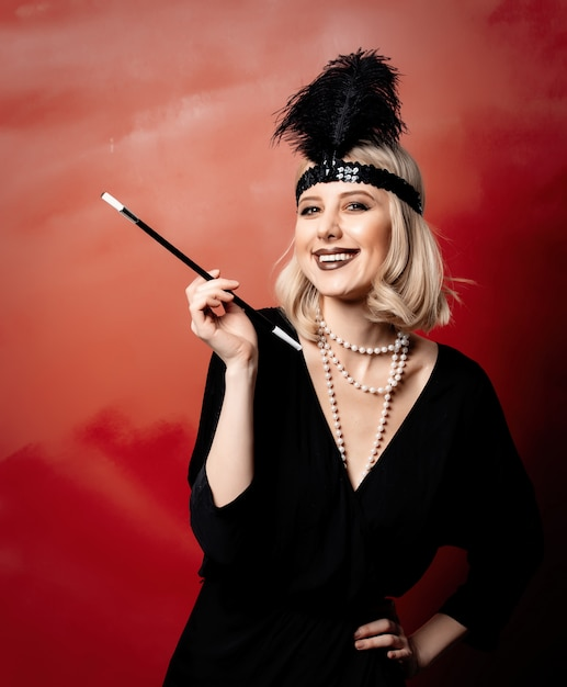 Mooie blondevrouw in de jaren 20kleren met rokende pijp op rode achtergrond Premium Foto