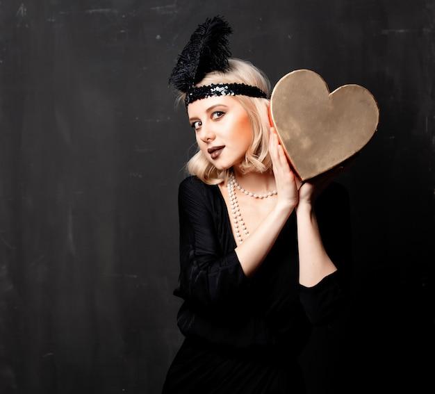 Mooie blondevrouw in de jaren 20kleren met valentine day-gift Premium Foto