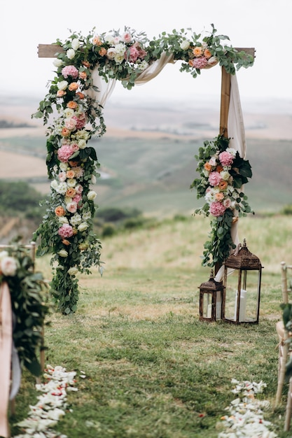 Mooie boog die in openlucht met bloemensamenstelling wordt verfraaid Gratis Foto