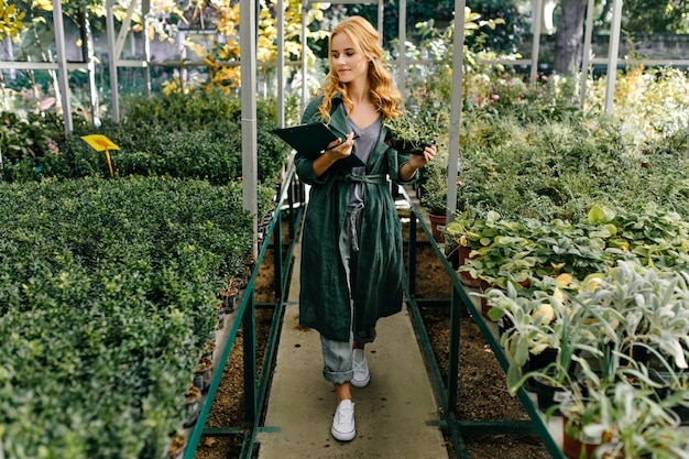 Mooie botanische tuin, gevuld met veel groene bloemen en struiken. meisje met blond krullend haar, poseert en presenteert zichzelf als bioloog. Gratis Foto