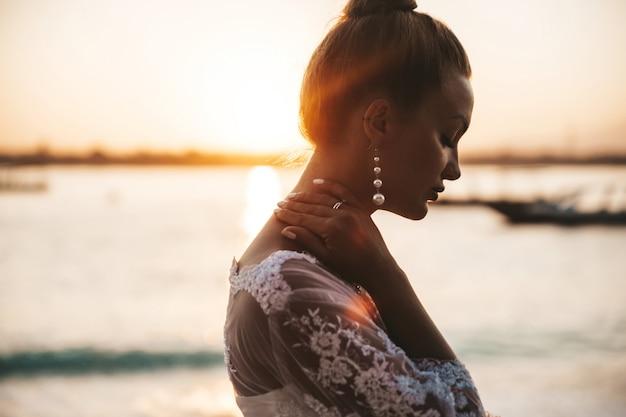 Mooie bruid die zich voordeed op het strand achter zee bij zonsondergang Gratis Foto