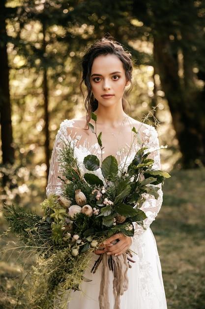 Mooie bruid in een witte jurk met een boeket op de achtergrond van een bos Premium Foto