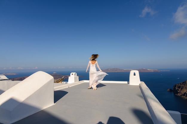 Mooie bruid in een witte jurk poseren op het dak van het huis tegen de achtergrond van de middellandse zee in thira, santorini. Premium Foto