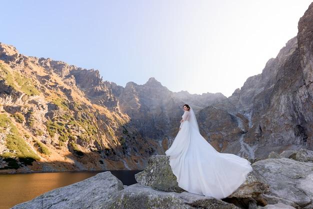 Mooie bruid in luxe jurk staat op de steen in de buurt van het hooglandmeer op de warme zonnige dag Gratis Foto
