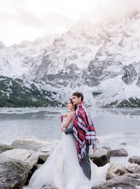 Mooie bruidspaar bedekt met heldere deken staat voor bevroren meer omgeven met besneeuwde bergen Gratis Foto