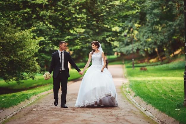Mooie bruidspaar. bruid en bruidegom in trouwdag buiten wandelen in het voorjaar de natuur. bruidspaar jonggehuwde gelukkige vrouw en man die een groen park omhelzen. Premium Foto