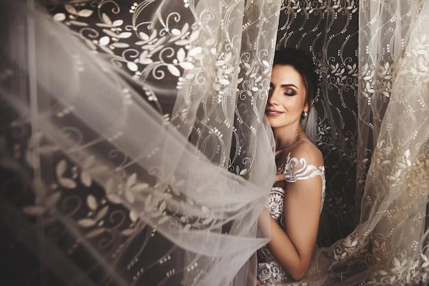 Mooie bruidstijl. bruiloft meisje staan in luxe trouwjurk in de buurt van venster Premium Foto