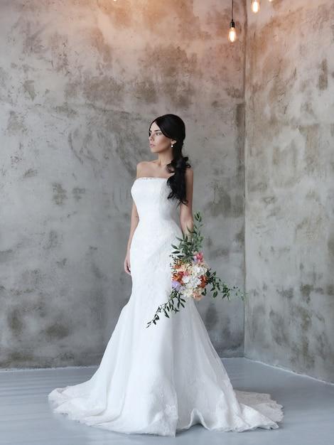 Mooie bruidvrouw die in huwelijkskleding een boeket van bloemen houdt Gratis Foto