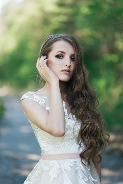 Mooie brunette bruid met krullen, make-up en stijlvolle jurk. portret op de muur van groene bomen. zomer trouwdag. Premium Foto