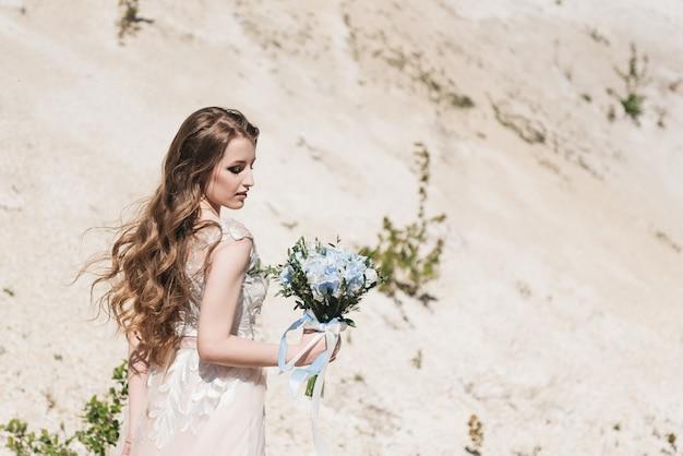 Mooie brunette bruid met vliegende krullen op de achtergrond van een zanderige berg in een stijlvolle jurk en een blauw en wit boeket. Premium Foto