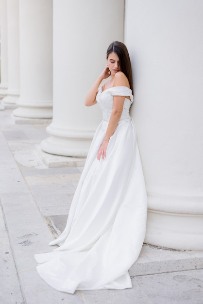 Mooie brunette bruid staat in de buurt van de enorme witte kolom Gratis Foto