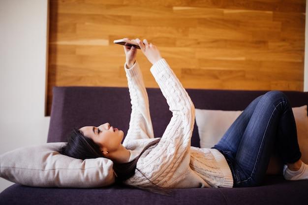 Mooie brunette die een selfie met haar slimme telefoon thuis bij wit hoofdkussen nemen Gratis Foto