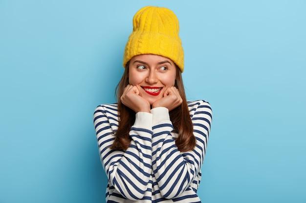 Mooie brunette duizendjarige vrouw houdt handen onder de kin, bijt op de lippen, heeft tevreden uitdrukking, draagt gele hoed en gestreepte trui Gratis Foto