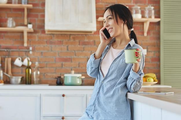 Mooie brunette huisvrouw verveelt zich thuis, babbelt lange tijd via smartphone Gratis Foto