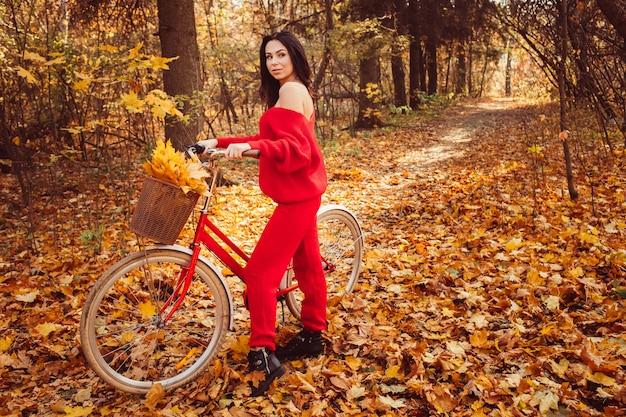 Mooie brunette in de herfst bos met een fiets Premium Foto