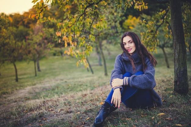 Mooie brunette in een gebreide trui zittend onder de boom in een herfst park Premium Foto