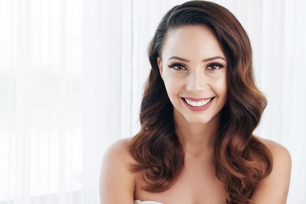 Mooie brunette met make-up, golvend haar en blote schouders poseren en glimlachen Gratis Foto