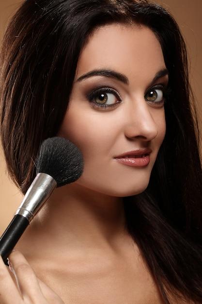 Mooie brunette met make-upborstel Gratis Foto