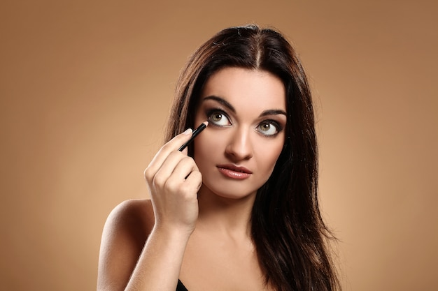 Mooie brunette met make-uppotlood Gratis Foto