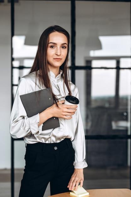 Mooie brunette met papieren in haar en kopjes koffie, werkzaam bij de official Premium Foto