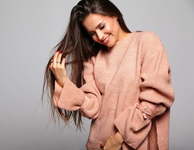 Mooie brunette model in casual beige warme trui spelen met haar Gratis Foto