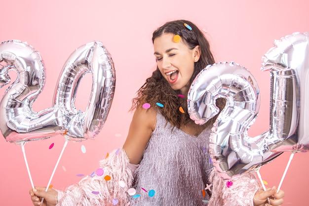 Mooie brunette partij meisje met krullend haar en feestelijke kleding poseren op een roze studio achtergrond met confetti en zilveren ballonnen voor het nieuwe jaar concept te houden Gratis Foto