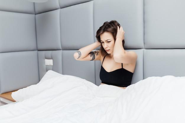 Mooie brunette toont ongezonde blik in de ochtend na het slapen in haar brede bed Gratis Foto