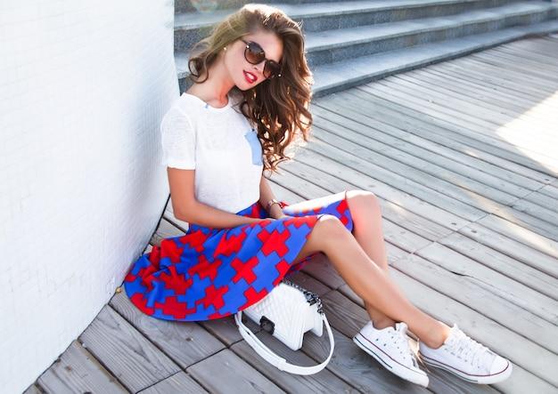 Mooie brunette vrouw met lang golvend haar zittend op straat Gratis Foto