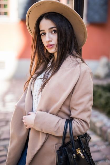 Mooie brunette vrouw met lang haar wandelen langs de straat gekleed in casual herfst kleding Gratis Foto