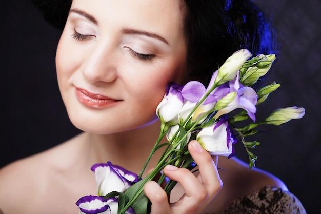 Mooie brunette vrouw met lila bloemen Premium Foto