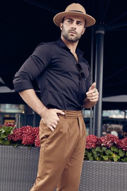 Mooie brute gebruinde gespierde hipster man die zich voordeed in de straten Premium Foto