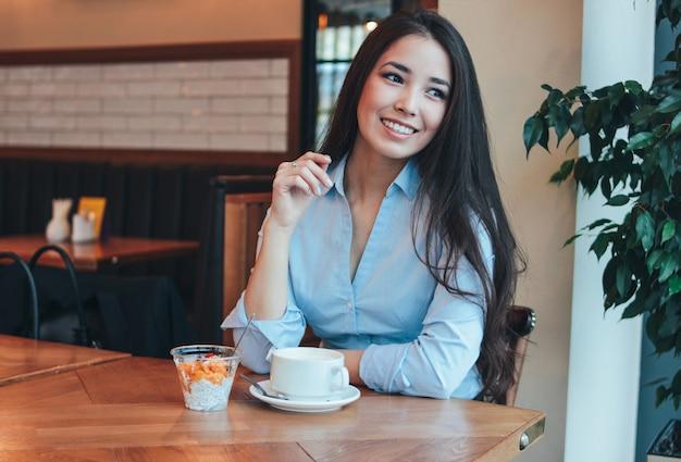 Mooie charmante brunette lachende aziatische meisje heeft ontbijt met koffie en chia pudding in café Premium Foto