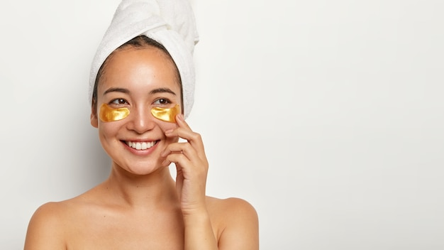 Mooie charmante vrouw met een gezonde huid, past cosmetische pleisters onder de ogen toe, kijkt graag opzij, denkt aan iets aangenaams, draagt een gewikkelde handdoek op het hoofd, heeft thuis spa-procedures Gratis Foto